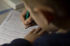 Het kind lost wiskundevoorbeelden op stock foto