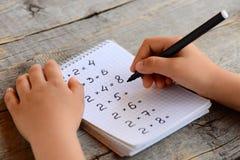 Het kind lost wiskundevoorbeelden op Het kind houdt een teller in zijn hand en schrijft antwoorden aan vermenigvuldigingsvoorbeel Royalty-vrije Stock Afbeelding