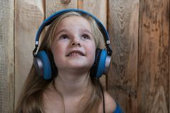 Het kind luistert aan de houten achtergrond van het muziekkind luisterend aan muziek royalty-vrije stock foto's