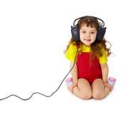 Het kind luistert aandachtig aan muziek op wit stock foto's