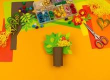 Het kind maakt ambachtboom van document Oranje achtergrond en materialen voor creatieve klassen stock fotografie