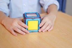 Het kind maakt een huis van de ontwerper, spelen, de handen van kinderen, kleurrijke heldere ontwerplijst stock fotografie