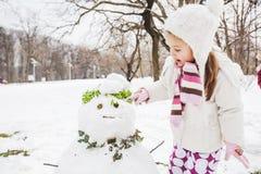 Het kind maakt een Sneeuwman in het Park bij de Winterdag royalty-vrije stock foto