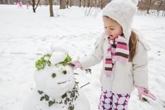 Het kind maakt een Sneeuwman in het Park bij de Winterdag royalty-vrije stock fotografie