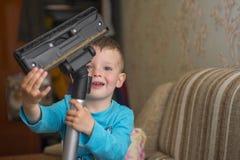 Het kind maakt het huis met een stofzuiger schoon stock foto