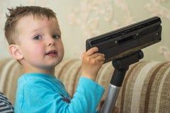Het kind maakt het huis met een stofzuiger schoon royalty-vrije stock afbeelding