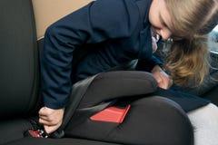 Het kind maakt onafhankelijk een veiligheidsgordel vast terwijl het zitten in een kindzetel in een auto royalty-vrije stock fotografie