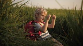 Het kind maakt schetsen van dromen in notitieboekje in groen gras stock video