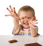 Het kind met een chocolade Stock Afbeelding