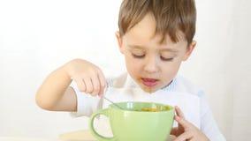 Het kind met genoegen eet soep van schotels met een lepel, close-up Een jongen eet zitting bij een lijst aangaande een witte acht stock videobeelden