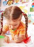 Het kind met krijt trekt in speelkamer. stock fotografie
