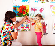 Het kind met leraar trekt verven in speelkamer. stock foto