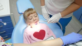 Het kind met leugens met open mond op tandleunstoel bij behandeling door arts met instrumenten dient binnen kliniek in stock video