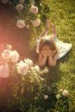 Het kind met leuke glimlach bij het tot bloei komen nam bloemen toe De groei en het bloeien Onschuld, zuiverheids en de jeugdconc stock foto