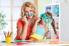 Het kind met moeder heeft een pret verwijderend schaar Stock Foto's