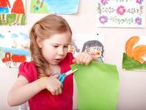 Het kind met schaar sneed thuis document. Stock Afbeelding