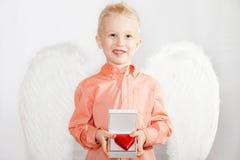 Het kind met vleugels van een engel houdt de doos in hart Stock Fotografie
