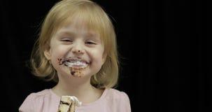 Het kind met vuil gezicht eet banaan met gesmolten chocolade en slagroom stock videobeelden