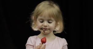 Het kind met vuil gezicht van gesmolten chocolade en slagroom eet aardbei stock footage