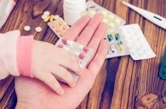 Het kind neemt de geneeskunde van de handen van de ouder royalty-vrije stock afbeeldingen