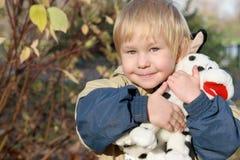 Het kind omhelst een stuk speelgoed Stock Foto