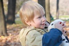 Het kind omhelst een stuk speelgoed Stock Afbeelding