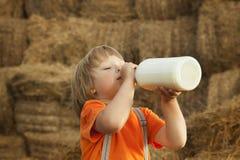 Het kind op een hooiberg drinkt melk Stock Foto