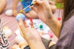 Het kind overhandigt het schilderen paaseieren met familie Stock Foto's