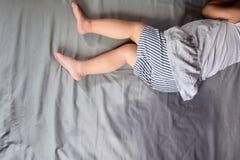 Het kind plast op een matras, Meisjevoeten en plast in bedblad, het concept van de Kindontwikkeling, geselecteerde nadruk bij nat Stock Afbeeldingen