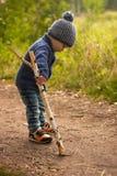 Het kind plukt de grond met een stok Stock Fotografie
