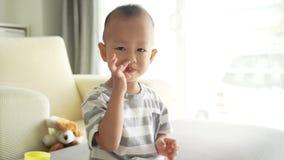 Het kind plukt zijn neus stock videobeelden