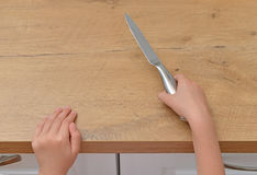 Het kind probeert om een keukenmes te krijgen Stock Afbeelding