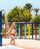 Het kind in rode bikini neemt douche. Stock Afbeeldingen
