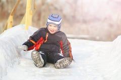 Het kind rolt de heuvel op de sneeuw naar beneden Stock Afbeelding