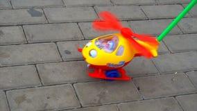 Het kind rolt een stuk speelgoed helikopter in het park stock footage