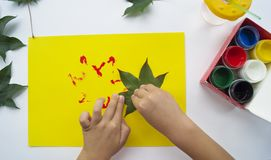 Het kind schildert een beeld van de herfstblad met verven royalty-vrije stock foto's