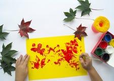 Het kind schildert een beeld van de herfstblad met verven stock afbeeldingen