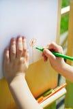 Het kind schildert een bloem op een blad van document Royalty-vrije Stock Foto