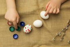 Het kind schildert eieren voor Pasen royalty-vrije illustratie