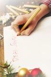 Het kind schrijft de brief aan Santa Claus Kind` s handen, het blad van document, potloden en Kerstmisdecoratie Stock Foto