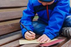 Het kind schrijft een pen in openlucht op papier royalty-vrije stock fotografie