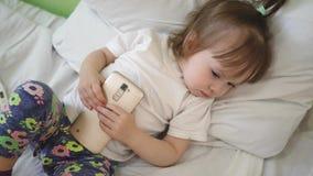 Het kind slaapt op hoofdkussen en houdt een tablet Leuke babyslaap in bed met smartphone stock videobeelden
