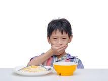 Het kind sluit met de hand zijn mond tussen het hebben van lunch Stock Foto
