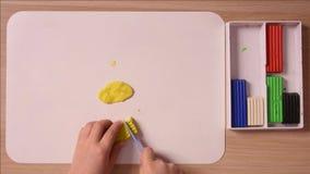 Het kind snijdt stuk van een stapel van gele plasticine voor ambachten af, close-up, hoogste mening stock footage