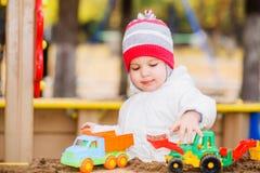 Het kind speelt auto's op de speelplaats Royalty-vrije Stock Fotografie