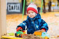 Het kind speelt auto's op de speelplaats Royalty-vrije Stock Foto
