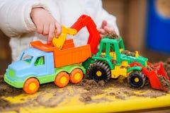 Het kind speelt auto's op de speelplaats Stock Afbeelding