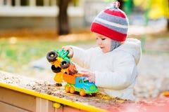 Het kind speelt auto's op de speelplaats Stock Foto