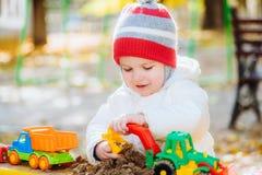 Het kind speelt auto's op de speelplaats Stock Foto's