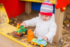 Het kind speelt auto's op de speelplaats Royalty-vrije Stock Afbeeldingen